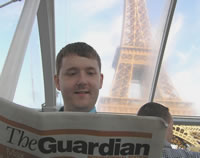 Paul reading the Guardian International Edition on a boat by the Eiffel Tower